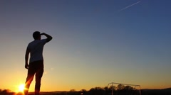 Silhouette of man looking up at plane trails in the sky, sunset Stock Footage