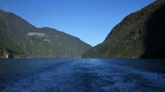 New Zealand Milford Sound mountains and blue wake from stern Stock Footage