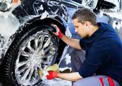 Man worker washing car's alloy wheels on a car wash - stock photo