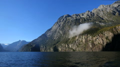 New Zealand Milford Sound patch of mist hangs on cliff ship mounted Stock Footage