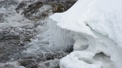 Long icicles hanging from snowy shelf over waterfall in northern norway Stock Footage