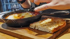 4K UHD time lapse video on eating Spanish baked egg and toast bread Stock Footage