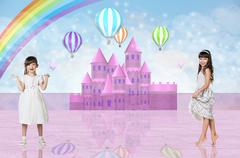 Two little girls in front of a pink fairy castle Stock Photos