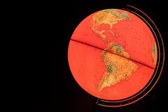 old red world globe illuminated from within - stock photo
