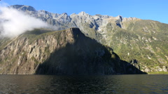 New Zealand Milford Sound protruding cliff from moving boat Stock Footage