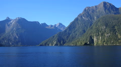 New Zealand Milford Sound cliffs rise from metallic blue water Stock Footage