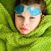 Sick child girl under a blanket - stock photo