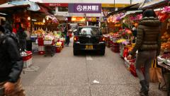 Following black car, drive through street market Stock Footage