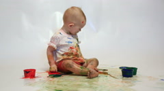 Little girl soiled by multi-colored paints sees on a white background Stock Footage