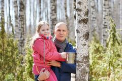 Family in the forest collecting birch sap Stock Photos