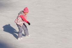 Little girl in winter clothes skating on ice rink Stock Photos