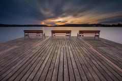 Beautiful long exposure lake with pier on foreground and bench. - stock photo