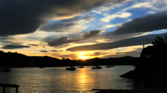 New Zealand Moeraki sunset boats and gold path on water Stock Footage