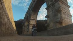 Couple of tourists in roman aqueduct Stock Footage