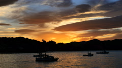 New Zealand Moeraki sunset glowing hills behind fishing boats Stock Footage