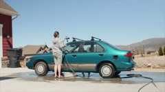 A mother washing a car with her cute toddler Stock Footage
