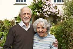Senior Couple Standing Outside Pretty Cottage - stock photo