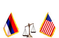 American and Russian flag with scales of justice Stock Photos