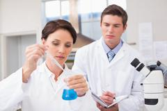 Scientists examining attentively pipette with blue fluid Stock Photos