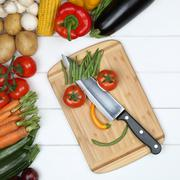 Vegetarian or vegan eating smiling face from vegetables on cutting board - stock photo