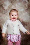 Cute little girl with blond hair and grey eyes laughs and dances - stock photo
