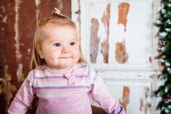 Cute blond little girl with big grey eyes and plump cheeks with pursed lips - stock photo