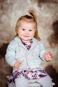 Sweet smiling little girl  sitting on chair and clapping her hands Stock Photos