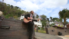 Man  plays guitar by wall and goes out along bridge Stock Footage