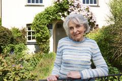 Senior Woman Standing Outside Pretty Cottage - stock photo