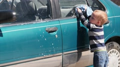 A toddler helping his mother wash a car Stock Footage