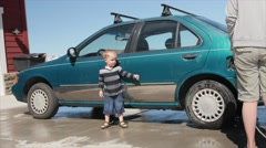 A mother washing car with her cute toddler Stock Footage