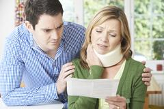 Couple Reading Letter In Respect Of Wife's Neck Injury Stock Photos