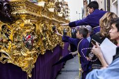 Boystries to touch the skirt of the throne to have good luck - stock photo