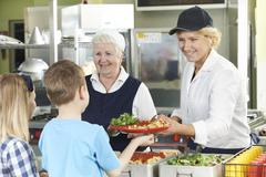 Pupils In School Cafeteria Being Served Lunch By Dinner Ladies Stock Photos
