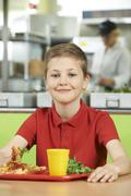 Male Pupil Sitting At Table In School Cafeteria Eating Healthy Lunch - stock photo