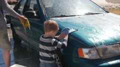 A toddler helping mother wash car Stock Footage