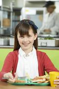 Female Pupil Sitting At Table In School Cafeteria Eating Unhealthy Lunch Stock Photos