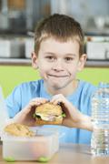 Male Pupil Sitting At Table In School Cafeteria Eating Healthy Packed Lunch Stock Photos