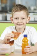Male Pupil Sitting At Table In School Cafeteria Eating Unhealthy Packed Lunch - stock photo