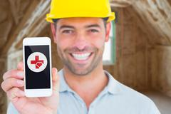 Composite image of portrait of smiling handyman showing smart phone Stock Photos