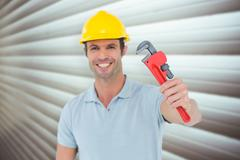 Composite image of happy carpenter holding monkey wrench Stock Photos