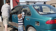 A toddler helping his mother wash car in driveway Stock Footage