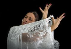 Flamenco dancer with white dress and hands crossed up on his back on black ba - stock photo