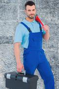 Composite image of repairman with toolbox and monkey wrench Stock Photos