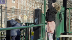 Girl swinging on monkey bars in Washington Square Park in 4K slow motion in NYC Stock Footage
