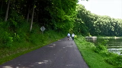 Bicyclist riding through rural community park Stock Footage