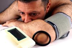 Man with automatic instrument for blood pressure measuring - stock photo