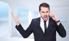Composite image of angry businessman gesturing on the phone - stock photo