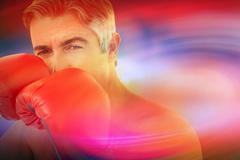 Stock Illustration of Composite image of fit man punching with boxing gloves