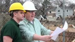 Architect and Construction Worker looking over plans on site Stock Footage